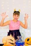 Muchacha del adolescente en el traje del demonio que presenta con las calabazas Fotos de archivo libres de regalías