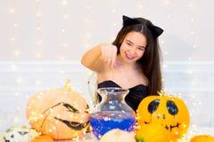 Muchacha del adolescente en el traje del gato que presenta con las calabazas Foto de archivo
