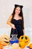 Muchacha del adolescente en el traje del gato que presenta con las calabazas Fotografía de archivo libre de regalías