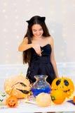 Muchacha del adolescente en el traje del gato que presenta con las calabazas Fotos de archivo