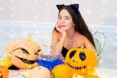 Muchacha del adolescente en el traje del gato que presenta con las calabazas Fotografía de archivo