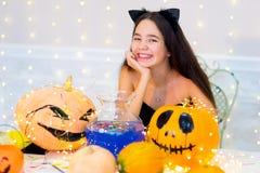 Muchacha del adolescente en el traje del gato que presenta con las calabazas Imagenes de archivo