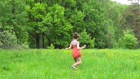 Muchacha del adolescente en el vestido anaranjado que corre en un prado verde