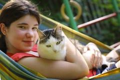 Muchacha del adolescente en hamaca con cierre del gato encima de la foto del verano Imágenes de archivo libres de regalías