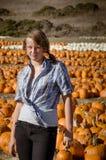 Muchacha del adolescente en la camisa de tela escocesa que elige las calabazas Imágenes de archivo libres de regalías