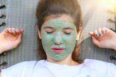 Muchacha del adolescente en la máscara azul del pegamento al aire libre Foto de archivo