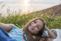 Muchacha del adolescente en la puesta del sol en el lado del mar Foto de archivo