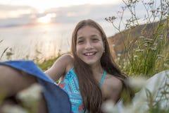 Muchacha del adolescente en la puesta del sol en el lado del mar Foto de archivo libre de regalías
