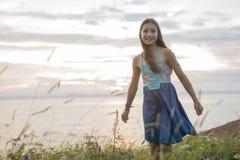 Muchacha del adolescente en la puesta del sol en el lado del mar Imagen de archivo libre de regalías