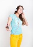 Muchacha del adolescente en los pantalones amarillos, escuchando la música de su smartphone Fotografía de archivo libre de regalías