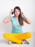 Muchacha del adolescente en los pantalones amarillos, escuchando la música de su smartphone Fotos de archivo