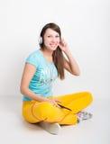 Muchacha del adolescente en los pantalones amarillos, escuchando la música de su smartphone Imágenes de archivo libres de regalías