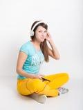Muchacha del adolescente en los pantalones amarillos, escuchando la música de su smartphone Foto de archivo