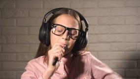 Muchacha del adolescente en música que escucha y el canto de los auriculares almacen de video