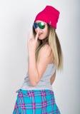Muchacha del adolescente en pantalones cortos del dril de algodón y una camiseta gris y un sombrero de punto rosado, atados en la Foto de archivo libre de regalías