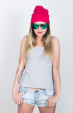 Muchacha del adolescente en pantalones cortos del dril de algodón y una camiseta gris y un sombrero de punto rosado, atados en la Fotografía de archivo