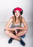 Muchacha del adolescente en pantalones cortos del dril de algodón y una camiseta gris y un sombrero de punto rosado, atados en la Imagen de archivo libre de regalías