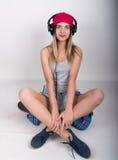 Muchacha del adolescente en pantalones cortos del dril de algodón y una camiseta gris y un sombrero de punto rosado, atados en la Imagenes de archivo