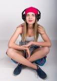Muchacha del adolescente en pantalones cortos del dril de algodón y una camiseta gris y un sombrero de punto rosado, atados en la Fotos de archivo libres de regalías