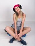 Muchacha del adolescente en pantalones cortos del dril de algodón y una camiseta gris y un sombrero de punto rosado, atados en la Imagen de archivo