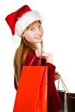 Muchacha del adolescente en sombrero de la Navidad con los bolsos de compras Foto de archivo libre de regalías