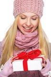 Muchacha del adolescente en sombrero y bufanda del invierno con la presentación de la caja Fotografía de archivo libre de regalías