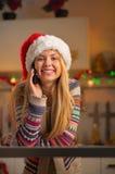 Muchacha del adolescente en teléfono celular del sombrero de santa que habla Imágenes de archivo libres de regalías