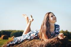 Muchacha del adolescente en un campo del otoño con la pila del heno Foto de archivo
