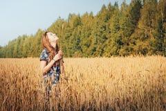 Muchacha del adolescente en un campo por completo de oídos amarillos Fotografía de archivo