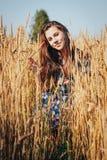 Muchacha del adolescente en un campo por completo de oídos amarillos Imágenes de archivo libres de regalías
