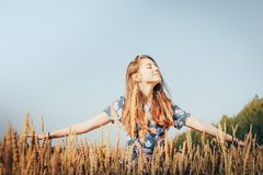 Muchacha del adolescente en un campo por completo de oídos amarillos Imagen de archivo libre de regalías