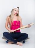 Muchacha del adolescente en un top rojo y una gorra de béisbol que sostienen un bate de béisbol el sentarse en un monopatín Imagenes de archivo