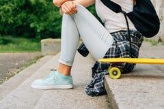 Muchacha del adolescente en vaqueros y una camisa de tela escocesa que se sienta en el ne de los pasos Foto de archivo