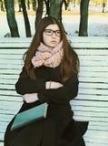 Muchacha del adolescente en vidrios con el pelo y el libro marrones largos Imagen de archivo libre de regalías