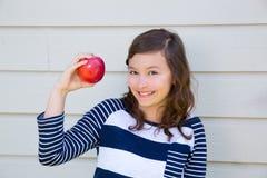 Muchacha del adolescente feliz comiendo una manzana Imagen de archivo libre de regalías