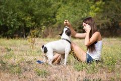 Muchacha del adolescente que alimenta su perrito Imagen de archivo libre de regalías