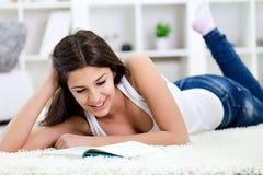 Muchacha del adolescente que aprende en suelo Imagen de archivo