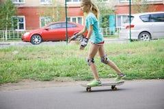 Muchacha del adolescente que aprende montar en el monopatín Fotografía de archivo