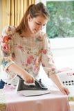 Muchacha del adolescente que ayuda con planchar en casa Imagen de archivo libre de regalías