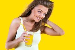 Muchacha del adolescente que bebe el zumo de naranja en fondo amarillo Fotografía de archivo