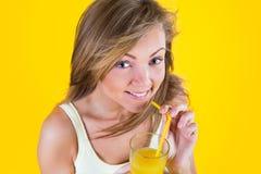 Muchacha del adolescente que bebe el zumo de naranja en fondo amarillo Imagenes de archivo