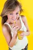 Muchacha del adolescente que bebe el zumo de naranja en fondo amarillo Foto de archivo