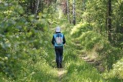 Muchacha del adolescente que camina en bosque en el día de verano, vista posterior Imagen de archivo
