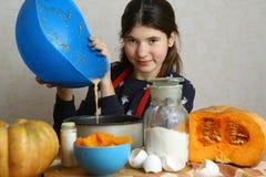 Muchacha del adolescente que cocina el pastel de calabaza Imagenes de archivo