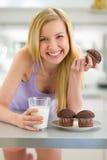 Muchacha del adolescente que come el mollete con leche en cocina Fotos de archivo