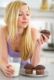 Muchacha del adolescente que come el mollete con leche en cocina Foto de archivo