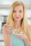 Muchacha del adolescente que come escamas con leche en cocina Foto de archivo