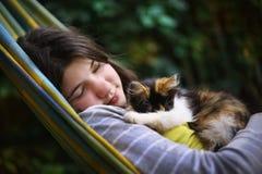 Muchacha del adolescente que duerme con el pequeño gatito tricolor en hamaca Imágenes de archivo libres de regalías