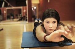 Muchacha del adolescente que ejercita en músculos traseros del gimnasio Imagen de archivo libre de regalías