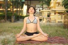 Muchacha del adolescente que ejercita yoga en la playa del seacost Fotografía de archivo